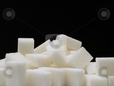 Sugar cubes stock photo, Close-up of white sugar cubes on a dark background. by FEL Yannick