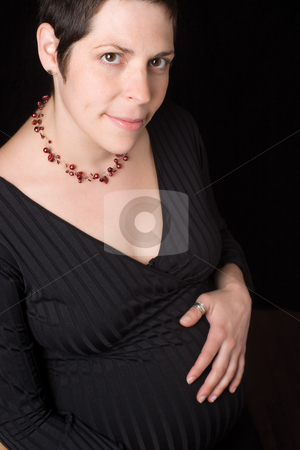 Pregnant women stock photo, Sitting portrait of a late twenty pregnant women with shy, holding her belly. looking at the camera by Yann Poirier