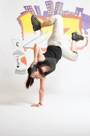B Girl Jumping stock photo, Late twentie hip hop women dancer on one hand by Yann Poirier