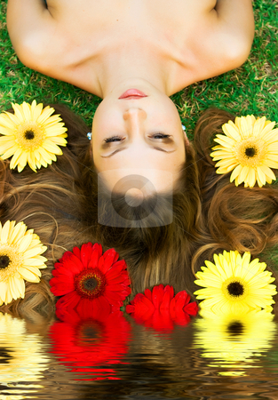 Brunette in flowers stock photo, Brunette girl lying on the glass with flowers and reflection in water by Dmitry Rostovtsev