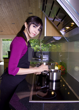 House wife cooking stock photo, House wife adding spices to the sauce while cooking in a modern kitchen by Daniel Kafer