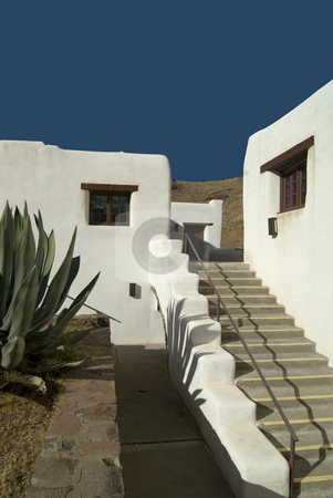 Adobe Hotel stock photo, White adobe walls of the hotel highlighted against a blue sky. by Charles Buegeler