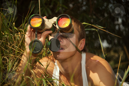 Secret  tracking. stock photo, The young man looks at the removed subjects through the field-glass. by Sergey Goruppa