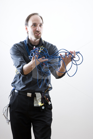 Frustrated by problem stock photo, Computer technician looking exaperated showing network cable by Yann Poirier