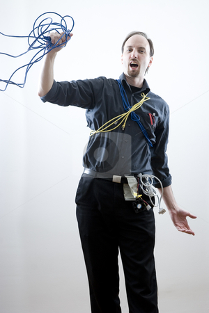 Falling technician stock photo, Computer technician, wearing many different kind of cables and wires, falling backwards holding on to a blue network cable by Yann Poirier