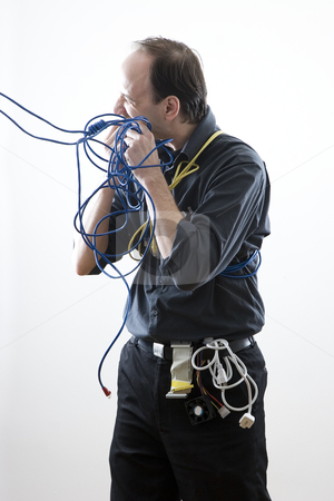 Cable technician eating cable stock photo, Cable technician taking a bite out of some blue network cable by Yann Poirier
