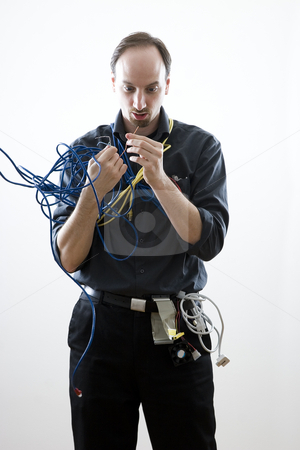 Dumb technician stock photo, Dumb technician surprise by wires in his hand by Yann Poirier