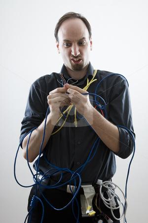 Dumb technician stock photo, Dumb technician lost by wires in his hand by Yann Poirier