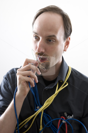 Eating wires stock photo, Computer technician cluess trying to eat network wire by Yann Poirier