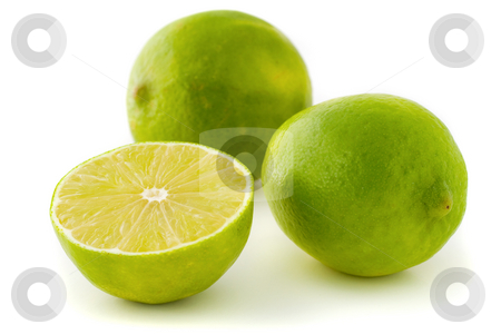 Green limes stock photo, Two whole limes and a half lime isolated on white background by Natalia Banegas