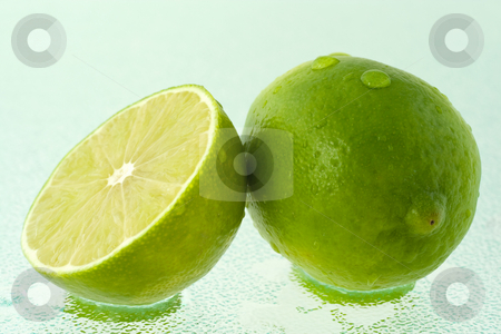 Lime and its half with water drops stock photo, A whole green lime and a half, covered by drops of water, on wet glass surface. by Natalia Banegas