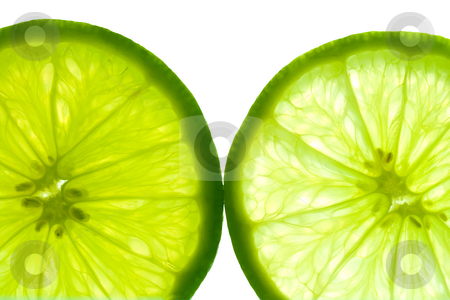 Close-up of two lime slices stock photo, Two green lime slices, backlit and isolated on white background. by Natalia Banegas