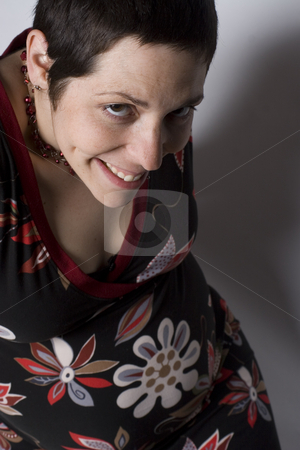 Boyish pregnant women looking naughty stock photo, Late twenties pregnant women with boyish look on white seamless sitting on ground level looking naughty by Yann Poirier