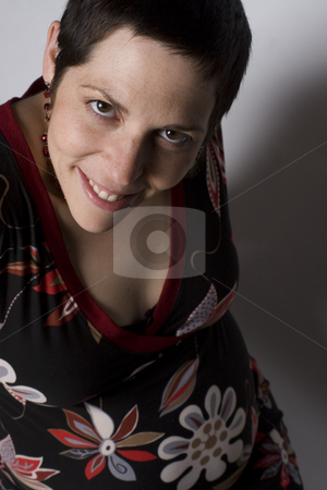 Boyish pregnant women loundging stock photo, Late twenties pregnant women with boyish look on white seamless sitting on ground level by Yann Poirier