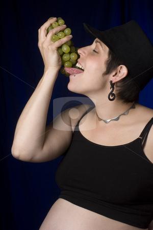 Eating grapes stock photo, Twenty something women in boyish look eating green grapes by Yann Poirier