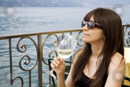 Woman drinking white wine  stock photo, Woman drinking white wine at an outside restaurant by Daniel Kafer