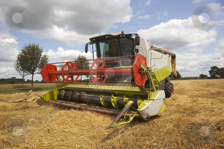 Harvest time stock photo, Image of combine harvester in a field of cut barley in summer by Mike Smith