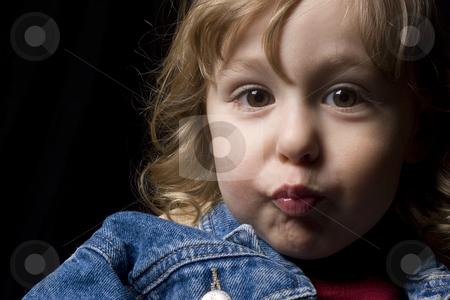 Kissy face stock photo, Portrait of a two year old boy wearing a jean jacket making a kissing face by Yann Poirier