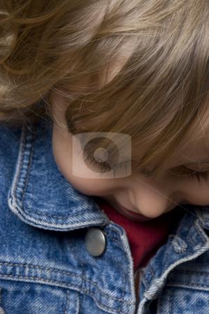 Two year old boy looking down stock photo, Portrait of a two year old boy wearing a jean jacket looking down by Yann Poirier