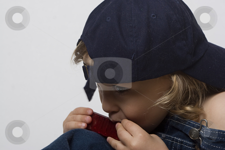 Toddle in overall and his harmonica stock photo, Two year old toddler playing with his harmonica in his jean overall by Yann Poirier