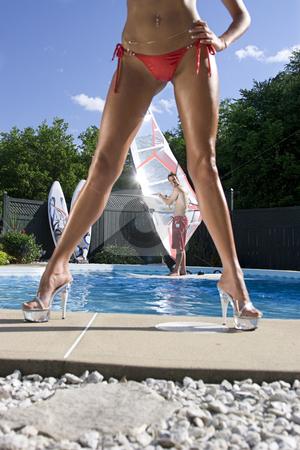 Windsurfer in pool stock photo, Windsurfer in a pool seen throught the legs of a model in a bikini by Yann Poirier