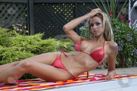 Women in bikini stock photo, Twenty something woment laying by the side of the pool in a red binikin by Yann Poirier