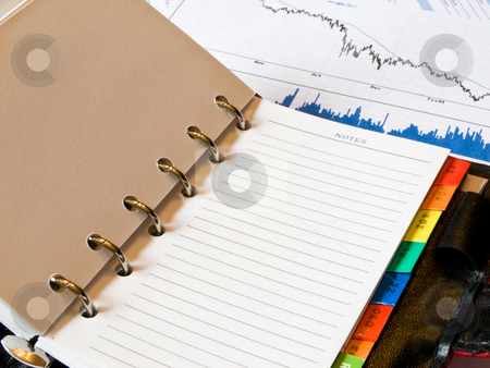 Financial crisis stock photo, Closeup of an opened agenda to a blank notes page.  An economic decreasing chart and analysis business histogram showing the crash is present in the background. by FEL Yannick