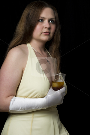 Teenager holding a drinking stock photo, Teenage girl in yellow evening dress with a drink in her hand by Yann Poirier