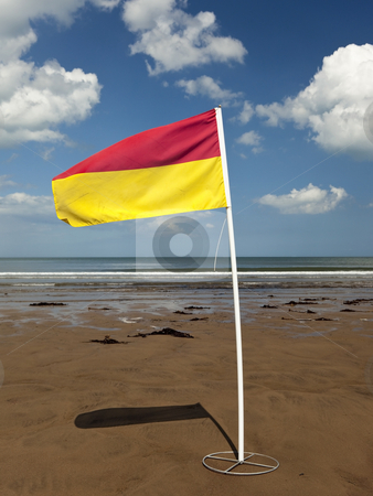 Red and yellow flag on a beach stock photo, A red and yellow flag marking the limit of the safe swimming area on a beach under a blue summer sky by Mike Smith