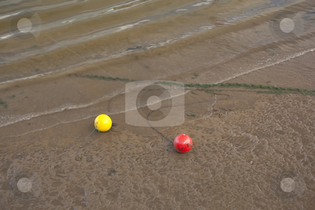 Mooring buoys stock photo, Two mooring buoys red and yellow attatched to chains in a harbour after the tide has gone out by Mike Smith
