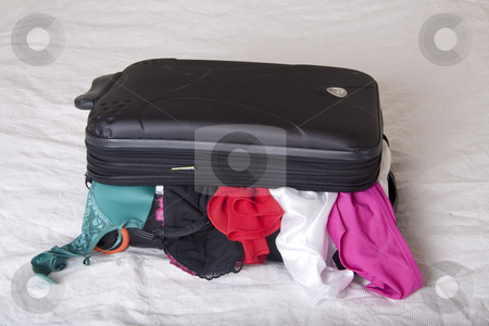 A full suitcase stock photo, Full suitcase on a bed with clothes hanging out of it by Daniel Kafer