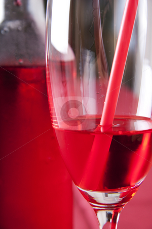 Red cocktail stock photo, Red cocktail in a glass with a straw and a bottle in the background by Daniel Kafer