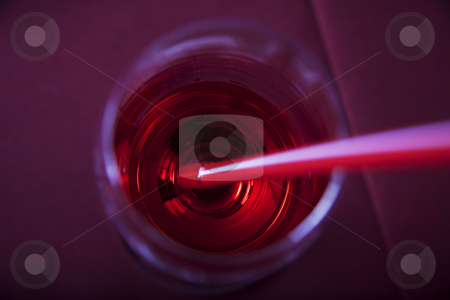 Red party cocktail stock photo, Red cocktail in a glass with a straw from above by Daniel Kafer