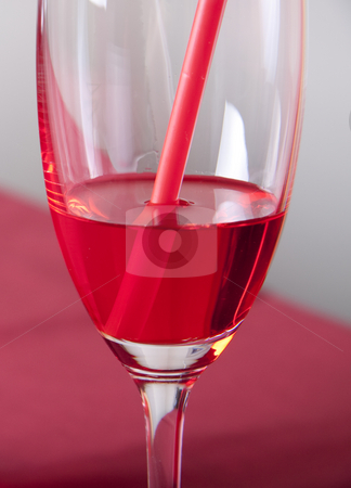 Red cocktail stock photo, Red cocktail in a glass with a straw on a red table by Daniel Kafer