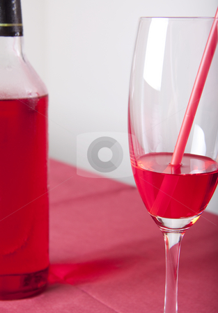 Red cocktail and bottle stock photo, Red cocktail in a glass with a straw and a bottle on a red table by Daniel Kafer