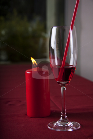 Red cocktail and candle stock photo, Red cocktail in a glass with a straw and a red candle in the background by Daniel Kafer