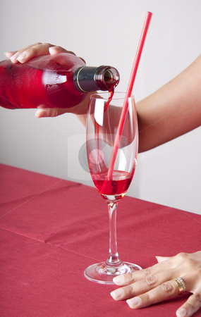 Red cocktail stock photo, Red cocktail in a glass with a straw and a bottle. The content of the bottle is poured into the glass. by Daniel Kafer