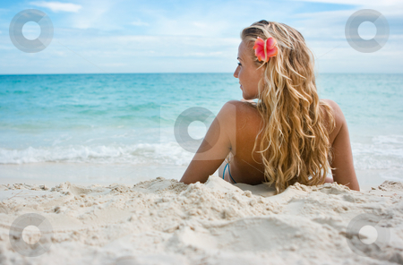 Girl with flower on the beach stock photo, Blonde girl sitting on white sand on the beach by Dmitry Rostovtsev