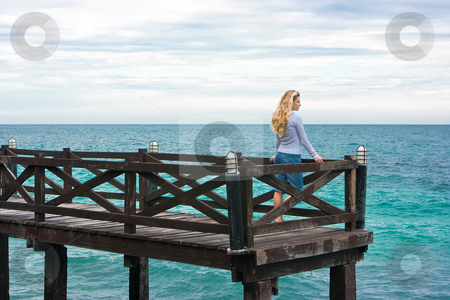 Serenity stock photo, Cute girl standing on the wooden pier by Dmitry Rostovtsev