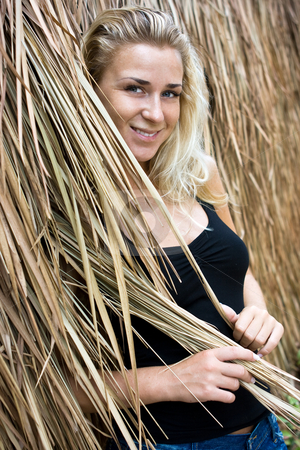 Girl in straws stock photo, Beautiful blonde girl standing at straw wall by Dmitry Rostovtsev