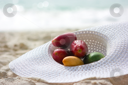 Fruits in hat stock photo, Different fruits lying in white hat on the beach by Dmitry Rostovtsev