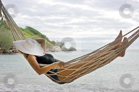 Lady in hammock stock photo, Lady with white hat lying in hammock on the sea beach by Dmitry Rostovtsev