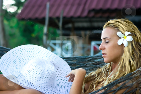 Hammock and lady stock photo, Blonde lady with white hat sitting in hammock by Dmitry Rostovtsev