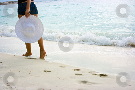 Lady with hat stock photo, Lady standing on the beach with white hat in hands by Dmitry Rostovtsev