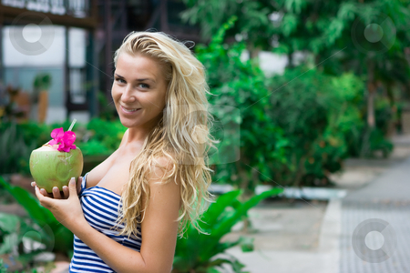 Blonde with coconut in hands stock photo, Blonde girl standing on the alley with coconut in her hands by Dmitry Rostovtsev