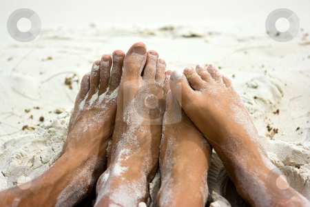 Feet on sand stock photo, Feet of young people getting together on the beach by Dmitry Rostovtsev