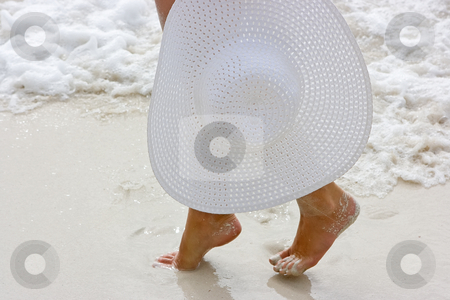Lady with white hat stock photo, Lady going along the beach with white hat in hands by Dmitry Rostovtsev