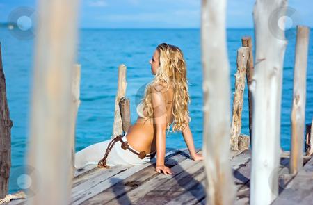 Blonde on pier stock photo, Blonde sitting on pier on a sunny day by Dmitry Rostovtsev