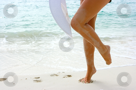 Woman with white hat on the beach stock photo, White hat in hands of a young lady on the beach by Dmitry Rostovtsev