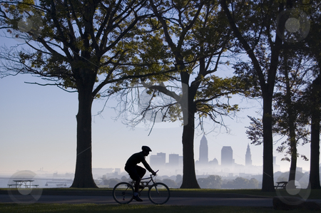 Biker on Foggy Morning stock photo, Silhouette of biker riding in park with trees and Cleveland skyline in background on a foggy morning. by Stewart Behra